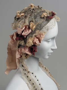 Mid-19th-c. woman's cap of blonde lace and silk roses. MFA.
