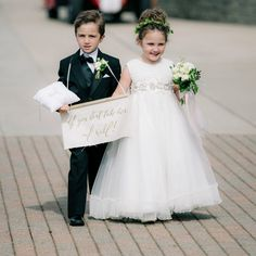 "Flower girl and ring bearer holding a wedding sign saying, ""If you don't take her, I will!"" http://www.stylemepretty.com/michigan-weddings/petoskey/2016/08/16/elegant-yacht-club-wedding-with-a-dreamy-designer-dress/ Photography: Clane Gessel - http://www.clanegessel.com/"