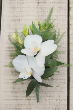 Bruidegomcorsage. Witte orchidee (Phalaenopsis), witte freesia. www.meesterlijkgroen.nl