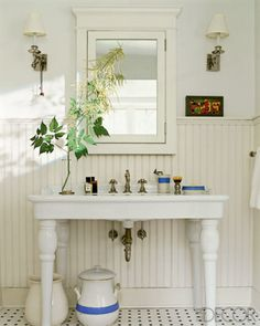 Handsome sconces flank a vanity mirror beautifully (lookbook.elledecor.com), but I love the wainscoting paired with this sink!