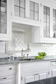 Above a sink or a cooktop, use border pieces to set off a smaller field of different tile. For this all-white subway-tile backsplash, a floral border surrounds square tile laid in a diamond pattern, helping draw the eye to the sink's period-style fixtures.