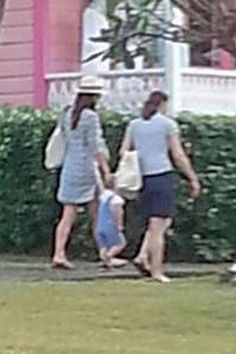 Kate Middleton, in sun hat on left, on a stroll with baby George and an unidentified pal.