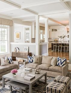 Love open floor plan, gray and beige colors and centered family room furniture.  Instead of entering into kitchen or family room, they created a half wall entry against which a console faces the family room. Love the comfortable family room furniture, coffee table under coffee table, the way the entry hides the working part if the kitchen and the clear view of the kitchen island.