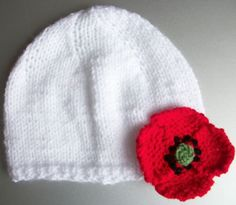 White baby hat. Choose rose or poppy trim, £7.99