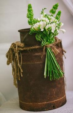 Old milk can with country flowers tied on with twine as wedding decor.