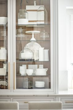 Doing a little spring cleaning or what we like to call spring re-styling and rearranging on the cabinets this week....went for the lots of white pieces to try to keep it clean, simple, and pop against the darker wood in the back! | Kitchen Living | Styled and Photographed by Public 311 Design | #builtinkitchenhutch #kitchenhutch #glasscabinets #kitchencabinets #whitecabinets #modernfarmhousekichendecor #builtincabinets