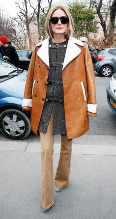 2015: Olivia Palermo wears a herringbone top layered underneath a draped leather coat, flared pants, and suede heels