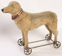 """MOHAIR RIDING DOG STUFFED TOY Sold For $ 180 Almost certainly by Steiff, in yellow mohair with sawdust filling and mounted on steel frame with 4 cast iron wheels, circa 1890-1910, 22"""" long x 18"""" high.                             Condition report           Moderate wear to mohair, missing ears and eyes."""