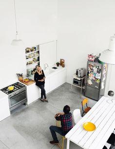 Helles Loft mit offener Küchenzeile auf grauem Betonboden