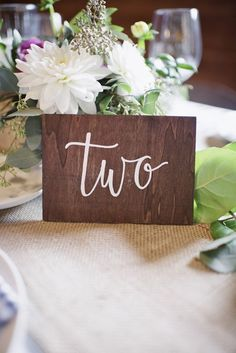 Modern hand calligraphy table numbers on dark wooden blocks {Photo by Basia}
