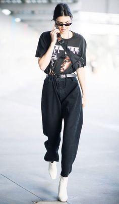 Kendall Jenner escolheu uma camiseta podrinha preta, baggy jeans de preto e bota branca.