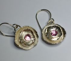 Argentium sterling silver hand forged earrings with 6 mm pink sapphire cabochon. The finish is a combination of shiny and brushed. These measure approximately 3/4 inch x 3/4 inch.