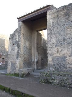 Entrance to the House of Octavius Quartio, Pompeii. Before the eruption, the spaces on either side of the entrance would have been rented to vendors. The benches near the front door may have been for waiting clients and visitors. The front doors are casts of the originals.