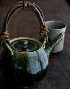 green ceramic teapot with twig handle