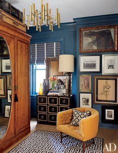 The dressing room of this apartment features a floor-to-ceiling mix of drawings and photographs as well as a 1960s chandelier and a Jonathan Adler rug.