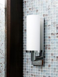 Distinctive light fixtures make a style statement in the bathroom. Modern wall-mount sconces dress up walls and add essential lighting to the vanity area. The brown stain on the oak vanity and storage shelf complements both the tile and the flooring./