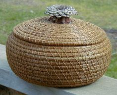 Lovely round basket with inverted pine cone handle lid and V stitch. The lid fits snugly onto the basket and is held in place by an inner coil. Linen Baskets, Rattan Basket, Pine Needle Crafts, Bountiful Baskets, Pine Needle Baskets, Round Basket, Pine Needles, Weaving Art, Weaving Techniques