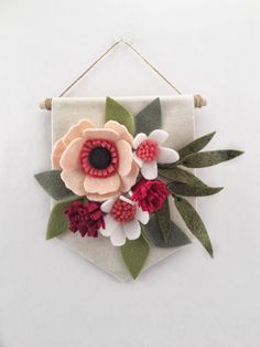 Felt Wildflower Banner   Made of soft and durable wool blend felt and high quality artist canvas.  This felt flower banner features flowers and leaves in shades of pink, red, and green on a canvas background. The banner is made from canvas wrapped around chipboard for extra stability. The back is finished with high-quality paper.  Flowers and leaves are handmade and arranged on a 6 W X 6 L banner. Banner comes ready to hang from thin jute twine and has a 3 hang length. Would be the perfect…