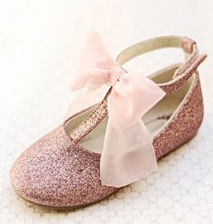 Every girl loves a bit of sparkle; our glitter T-straps offer this in an unusual silhouette and the perfect shade of blush pink. They feature a soft chiffon bow and velcro ankle strap. Eco-friendly soles. They include a matching blush chiffon clip.