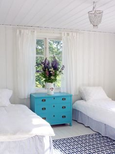 This HGTV fan saved the windows from an old house nearby and installed them to create a source of natural light in this bedroom.  She then painted the floor, walls and ceiling stark white and integrated color through her use of accessories. The most eye-catching piece in the room, the nightstand chest, was a vintage find that she painted a vibrant turquoise hue for practically nothing. Other repurposed and salvaged finds include the wooden blue and white desk as well as the matching chair.