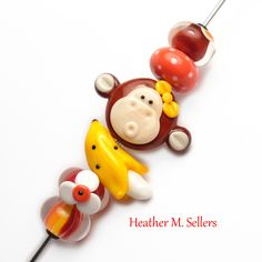 That's Bananas No. 4, a set of lampwork glass beads which includes a silly monkey and banana. Created by Heather Sellers #monkey #banana