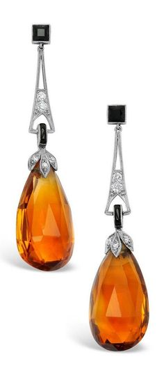 An Art Deco Pair of Citrine, Diamond, Onyx and Platinum Ear Pendants, circa 1920. The elongated designs suspending a pair of citrine briolettes weighing approximately 28.00 carats, from diamond-set floral caps topped by a tapering line accented by round diamonds, onyx accents, mounted in platinum. #ArtDeco