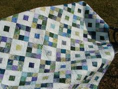 This lap quilt measuring 48x60 is constructed in a cool colorway of batiks in aqua, purples, greens, and blues. The quilt would also make a good