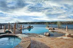 This infinity pool features raised spa, bridge, and tanning ledge with boulder accents. Elite Pools by Scott, Little Rock, Arkansas http://www.luxurypools.com/builders-designers/elite-pools-by-scott.aspx