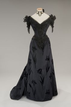 Tirelli Costumi, evening gown in black satin with black velvet flowers in relief ; trimmed around the neckline with tulle and black jet embroidery, same beads at the waist and at the sleeves, by Piero Tosi, for Visconti's The Innocent, 1976