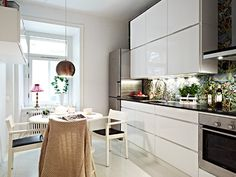 One of these kitchens for me please. Love the chairs, and the wall paper, the lamp and the whiteness.