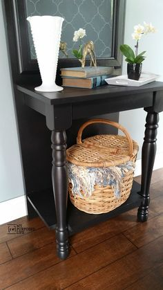 A thrifted mirror and cheap door are combined with a cabinet door to make an easy DIY  black entryway table.