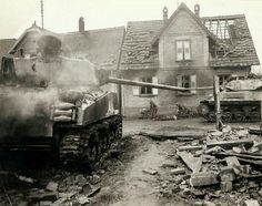 A tank destroyer moving past an American tank that was knocked out during the hot battle when the Americans retook the town