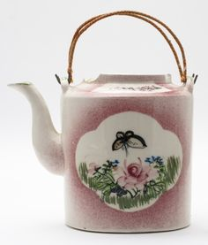 Tea pot as part of set contained in a basket secured with brass clasp. The pot is white and pink, with floral motifs | Horniman Museum and Gardens | CC0