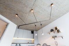 Po vstupu do obývacího pokoje zaujme přiznaný betonový strop a vedení elektrických kabelů ke svítidlům.