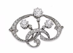 An Art Nouveau diamond brooch, Viennese Of stylised foliate design, the 'whiplash' scrolls set throughout with old round brilliant and rose-cut diamonds and terminating in three larger old round brilliant-cut diamonds, width 33mm, stamped '750', bearing Austro-Hungarian control marks for Vienna, drop lacking, the three principal diamonds estimated to weigh approximately 1.48cts in total