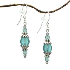 These beautiful dangle earrings feature shiny round aqua glass beads paired with silvertone pewter bead caps and spacers. Lightweight and comfortable, these fashionable earrings are finished with .925