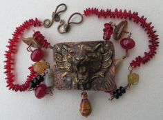 Brass tiger piece portraying a snarling tiger head, soldered  onto a piece of textured and torched copper.  Available here: http://www.jewelrybecause.com/#!deb-vintagesoul-bonner/c14w5