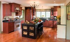 I want this island in my kitchen! Bread/potato drawer! Bar stool seating on one side, storage on the other!