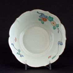 An 18th Century Chantilly Soft-Paste Porcelain Bowl in the Kakiemon Style c.1735-1740. The Shallow Form with Steep Sides and a Barbed and Indented Rim is Decorated in Typical Kakiemon Enamels. The Design is Quite Close to the Japanese Kakiemon Original with a Branch with Flowers and an Elongated Wavy Tendril with a Flower-Head at its Terminus. The Exterior Similarly Decorated. The Rim Dressed in Brown Enamel to Imitate Japanese Fuchibeni.