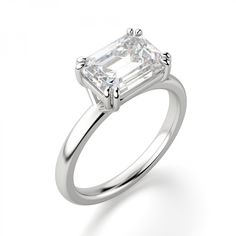 The beauty of a solitaire takes a new direction. A Contemporary Nexus Diamond™ that is traditionally vertical lays horizontally, making the stone look larger and fingers longer and more elegant. The double claw prongs intertwine from the setting around the stone and add an extra modern element to this fresh take on a classic. It's gorgeous as an engagement ring or transfers beautifully to the right hand as a cocktail ring.  Center stone pictured: 2.62 carat Emerald cut. Center stone avail...