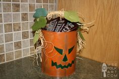 Paint old popcorn tins Jack-O-Lanterns