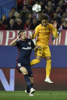 Barcelona's Brazilian forward Neymar (R) heads a ball next to Atletico Madrid's midfielder Saul Niguez during the Champions League quarter-final second leg football match Club Atletico de Madrid vs FC Barcelona at the Vicente Calderon stadium in Madrid on April 13, 2016.