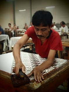 Waxing treatment: a man works using a heavy tool such as copper-stamps to apply wax to the fabric. Photo by Mari Sasmiro...