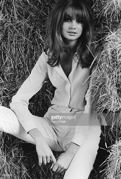 English supermodel Jean Shrimpton nestles into a haystack, circa 1970.