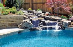 Swimming pool with flowing rock waterfall