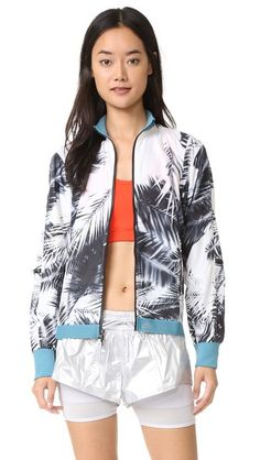 A lightweight adidas by Stella McCartney track jacket in a bold print. Zips close the placket and 3 pockets. Snug edges. Long sleeves with zip vents. Mesh lining.
