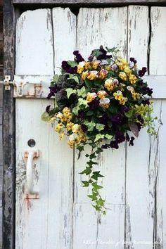 ドアに寄せ植えをハンギングするだけでフランスの片田舎の風情になります。