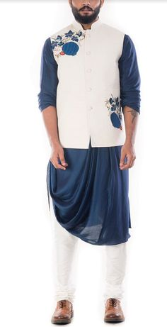 Featuring a royal blue cowl drapped kurta with a light cream nehru jacket and a white churidar. The jacket has beautiful floral embroidery on its yoke. Fabric specification: The kurta is made of cott. Mens Indian Wear, Mens Ethnic Wear, Indian Groom Wear, Indian Men Fashion, Mens Wedding Wear Indian, Groom Fashion, Fashion Suits, Mens Fashion, Indian Weddings