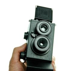 The camera has a unique appearance with a pair of vertically arranged lenses…