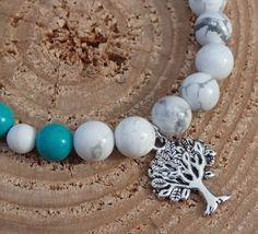 Přírodní bílý howlitový náramek se sinkiangským tyrkysem a ÓM Bílé howlitové korálky a pět korálků ze sinkiangského tyrkysu se symbolem ÓM a stromem. Na ženské ruce působí elegantně a čistě.  Velikost cca 18-19 cm, navlečeno na elastickém lanku.